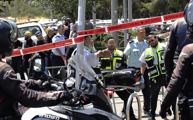 Israeli rescue workers remove the body of an alleged assailant in a stabbing attack in Jerusalem, May 24, 2021 (AP Photo/Mahmoud Illean)