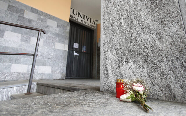 Flowers and a candle lie in front of the Stresa to Mottarone cable car departure station, in Stresa, northern Italy, May 24, 2021. (Antonio Calanni/AP)