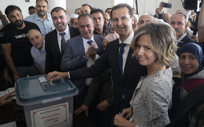 Syrian President Bashar Assad and his wife Asma vote at a polling station during the presidential elections in the town of Douma, in the eastern Ghouta region, near the Syrian capital Damascus, May 26, 2021. (AP Photo/Hassan Ammar)