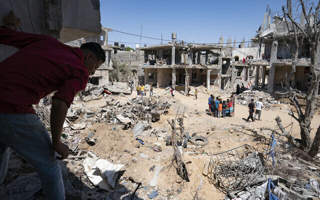 Neighbors gather in a clearing strewn with debris from an airstrike during an 11-day war between Gaza's Hamas rulers and Israel, in Beit Hanoun, Gaza Strip, May 26, 2021. (John Minchillo/AP)