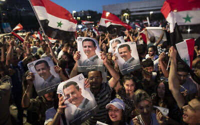 Syrians hold up national flags and pictures of Bashar Assad as they celebrate hsi election at Omayyad Square, in Damascus, Syria, Thursday, May 27, 2021. (AP/Hassan Ammar)