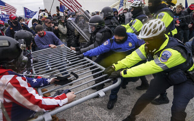 In this file photo from Jan. 6, 2021, Trump supporters beset a police barrier at the Capitol in Washington. (AP Photo/John Minchillo, File)