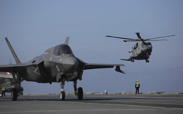 Military personnel direct F-35 jets and helicopters on the deck of the aircraft carrier HMS Queen Elizabeth as it participates in the NATO Steadfast Defender 2021 exercise off the coast of Portugal, May 27, 2021 (AP Photo/Ana Brigida)