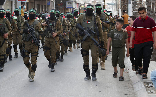 Children talk with masked members of the military wing of Hamas, while marching along the streets of Nusseirat refugee camp, central Gaza Strip, May 28, 2021. (AP Photo/Adel Hana)