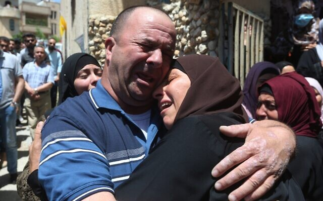 Bereaved relations of Ahmad Daraghme, an officer in the Palestinian Authority intelligence services killed by Israeli soldiers, weep at his funeral in his home village of Laban al-Sharqiya on Wednesday, May 12, 2021 (WAFA)