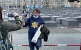 A man protests coronavirus restrictions with a yellow star and a photo of Anne Frank outside the Holocaust memorial in Berlin. (@ZSKberlin/Twitter via JTA)