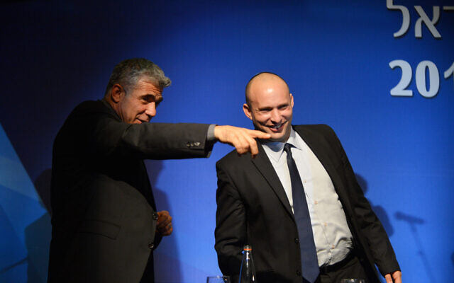 File: Then-finance minister Yair Lapid (left) and then-economy minister Naftali Bennett at the Manufacturers Association of Israel annual general assembly at the David Intercontinental Hotel in Tel Aviv, February 26, 2014. (Yossi Zeliger/Flash 90.)