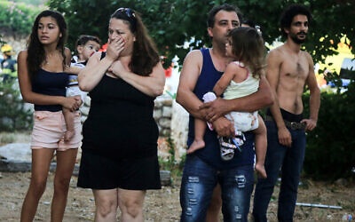 Residents look in shock, after a rocket directly hits a house in Ashkelon, southern Israel, early morning on August 26, 2014. (Flash90/File)