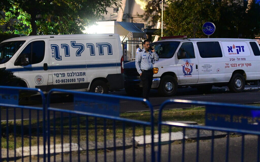 A police officer stands next to ambulances outside the Institute of Forensic Medicine in Tel Aviv, where the bodies of victims from the deadly crushing at Mount Meron are being identified, May 1, 2021. (Avshalom Sassoni/Flash90)