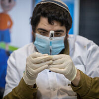 A medical worker prepares a COVID-19 vaccine injection, at a Clalit vaccination center in Jerusalem, on March 8, 2021. (Yonatan Sindel/Flash90)