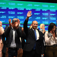 Yamina chair Naftali Bennett (C) and party members seen with supporters at a party event in Petah Tikva on March 23, 2021. (Avi Dishi/Flash90)