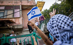 Palestinians and left-wing activists protest against the expulsion of Palestinian families from their homes in the East Jerusalem neighborhood Sheikh Jarrah, April 16, 2021. (Yonatan Sindel/Flash90)