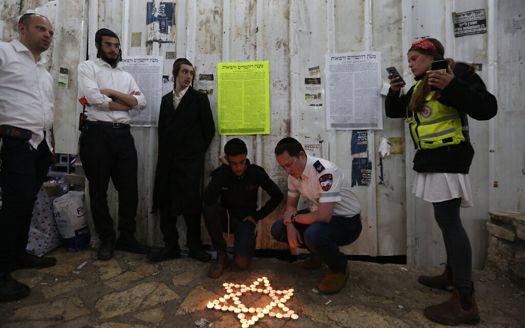 Ultra-Orthodox Jews light candles for the 45 victims of the deadly crush during Lag B'Omer celebrations at Mount Meron, at the scene of the fatal disaster. May 1, 2021. (David Cohen/Flash90)