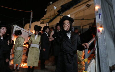 Ultra-Orthodox Jews light candles and mourn for the 45 victims of the deadly crush during Lag B'Omer celebrations at Mount Meron, at the scene of the fatal disaster. May 1, 2021. (David Cohen/Flash90)