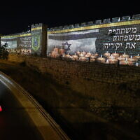 The Old City walls in Jerusalem are lit up with the Israeli flag and candles in memory of the 45 victims who were killed in fatal crushing at Mount Meron during Lag B'Omer celebrations, May 0, 2021. (Yonatan Sindel/Flash90)