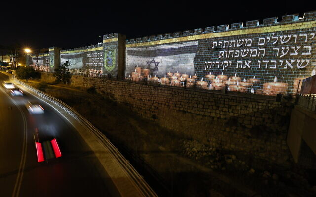 The Old City walls in Jerusalem are lit up with the Israeli flag and candles in memory of the 45 victims who were killed in a stampede at Mount Meron during Lag B'Omer celebrations, May 0, 2021. (Yonatan Sindel/Flash90)