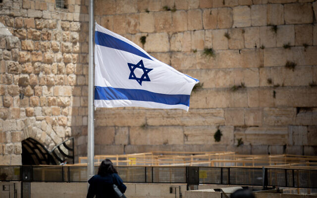People walk next to an Israeli flag lowered to half-staff in honor of the Mt. Meron disaster victims, at the Western Wall in Jerusalem's Old City, May 2, 2021 (Yonatan Sindel/Flash90)