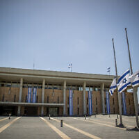 Israeli flags lowered to half-staff in honor of Mount Meron crush victims, at the Knesset in Jerusalem, May 2, 2021. (Yonatan Sindel/Flash90)