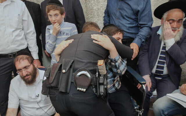 Police officer Rami Alwan hugs Shmuel Hayut, whom he saved at Meron. Father Avigdor Hayut sites to the left at their home in Bnei Brak, May 3, 2021 (Flash90)