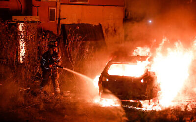 Firefighters put out a car of Jewish family that was set on fire in the East Jerusalem neighborhood of Sheikh Jarrah on May 6, 2021. (Olivier Fitoussi/Flash90)