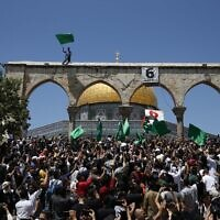 People hold Hamas flags as Palestinians gather at the Dome of the Rock after praying on the last Friday of Ramadan, to protest over the possible eviction of several Palestinian families from homes on land claimed by Jews in the east Jerusalem neighborhood of Sheikh Jarrah, May 7, 2021. (Jamal Awad/Flash90)
