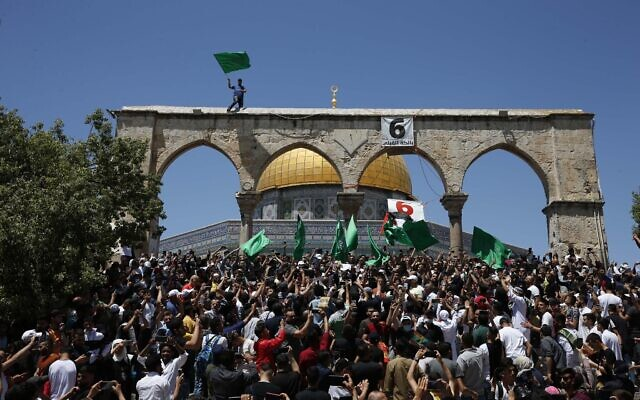 People hold Hamas flags as Palestinians gather at the Dome of the Rock after praying on the last Friday of Ramadan, to protest over the possible eviction of several Palestinian families from homes on land claimed by Jewish settlers in the east Jerusalem neighborhood of Sheikh Jarrah, May 7, 2021. (Jamal Awad/Flash90)