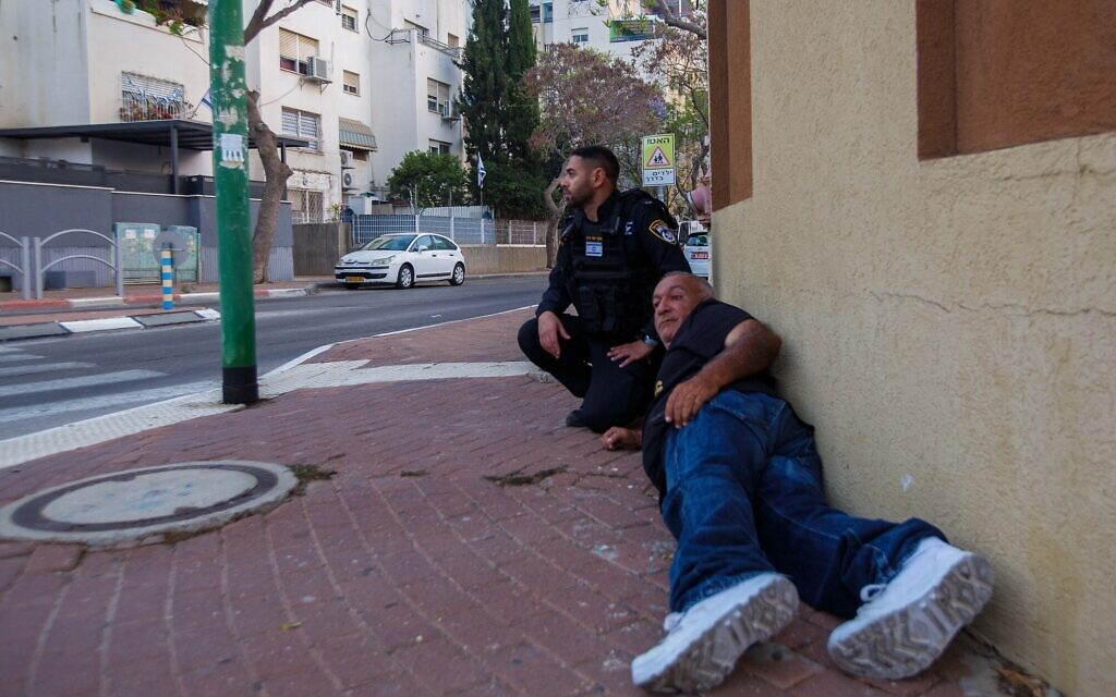 People shelter during a rocket siren in Ashkelon on May 11, 2021 (Edi Israel/Flash90)