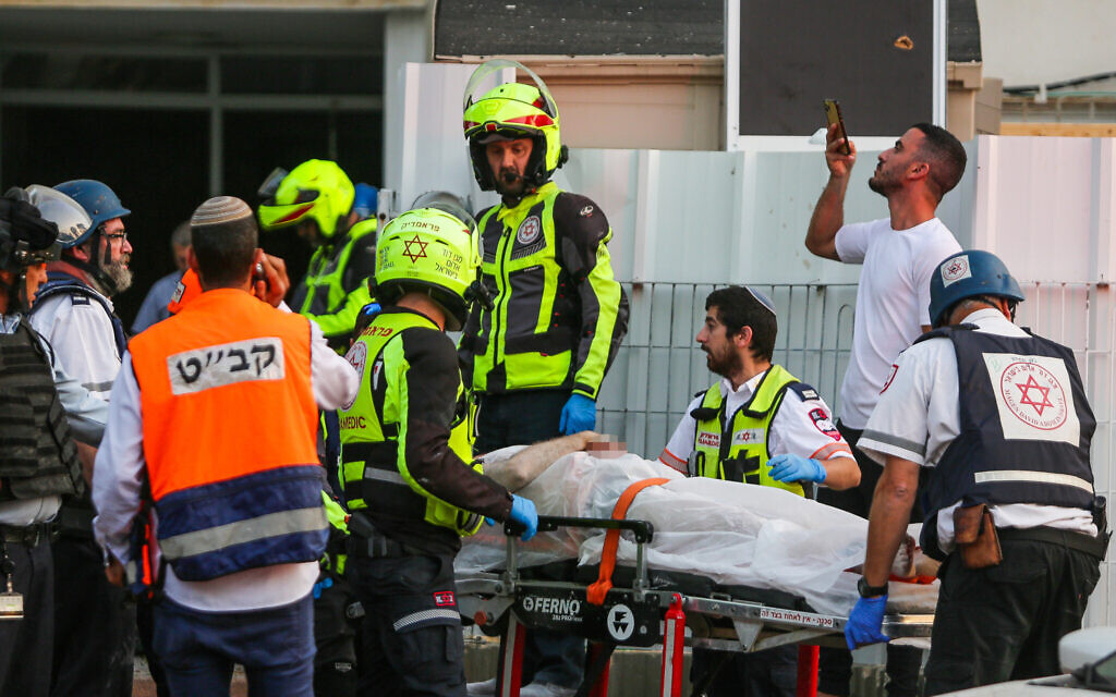 Medics evacuate an injured man at the scene where an apartment building was hit by a rocket fired from the Gaza Strip in Ashkelon, southern Israel, on May 11, 2021. (Edi Israel/Flash90)