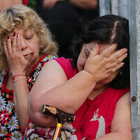 Women react at the scene where an apartment building was hit by a rocket fired from the Gaza Strip in Ashkelon, southern Israel, on May 11, 2021. (Edi Israel/Flash90)