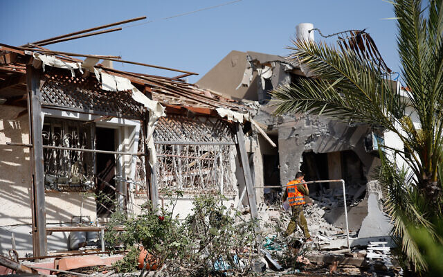 Israeli security forces at the scene where a rocket fired from the Gaza Strip hit a house in the southern Israeli city of Ashkelon, on May 11, 2021. (Flash90)