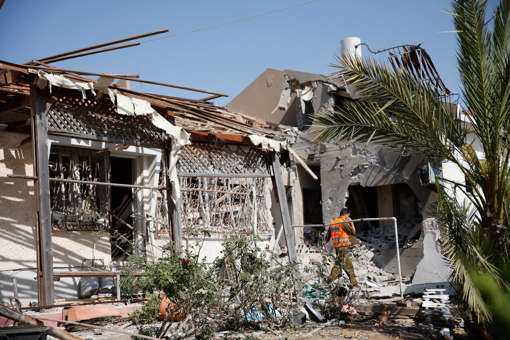 Israeli security forces at the scene where a rocket fired from the Gaza Strip hit a house in the southern Israeli city of Ashkelon