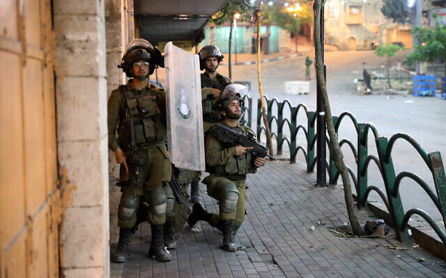 IDF soldiers prepare to engage during clashes with Palestians in the West Bank city of Hebron on May 12, 2021. (Wissam Hashlamoun/Flash90)