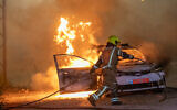A police patrol car on fire in the city of Lod, on May 12, 2021. (Yossi Aloni/Flash90)