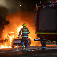 A firefighter is seen on the streets of the central city of Lod amid ongoing unrest, May 12, 2021 (Yossi Aloni/Flash90)