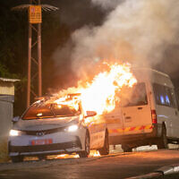 A police patrol care on fire in the city of Lod, May 12, 2021. (Yossi Aloni/Flash90)