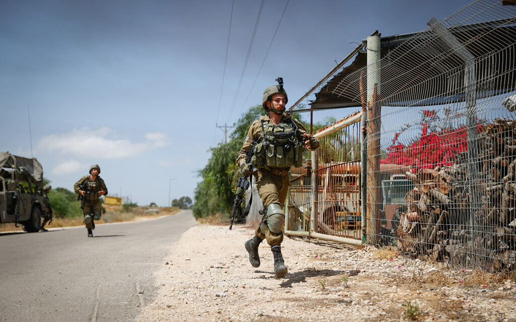 Israeli soldiers near the site of where a jeep was hit by an anti-tank missile fired from Gaza, May 12, 2021 (Yonatan Sindel/Flash90)