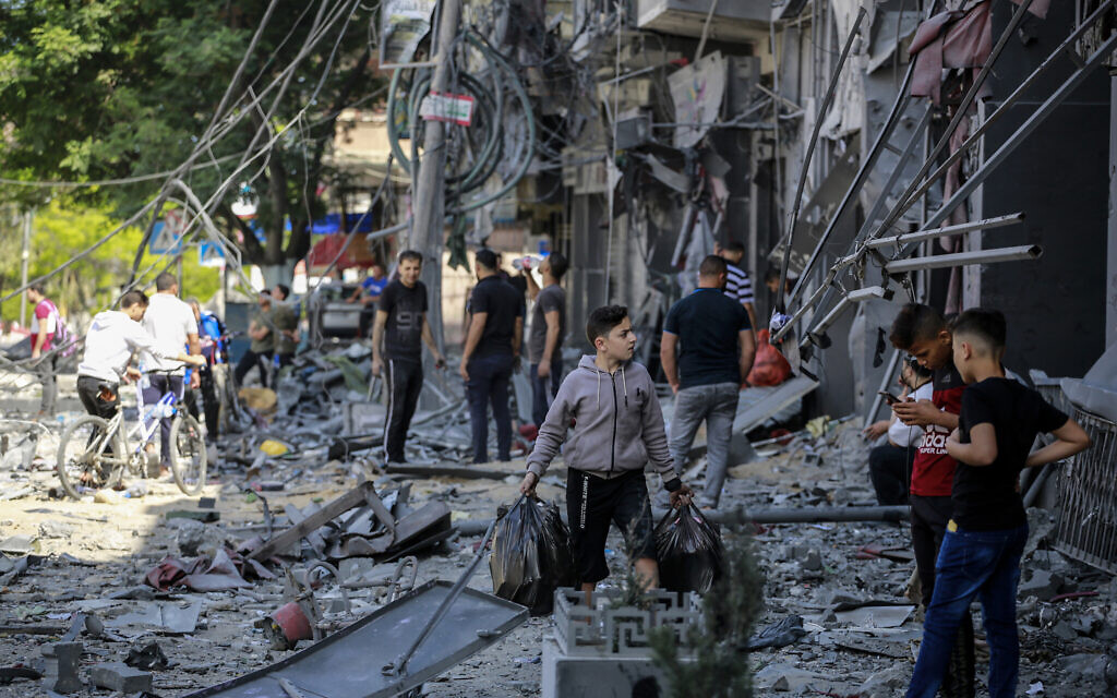 Palestinians check the damage caused after a 15-floor building was destroyed in an Israeli airstrike in Gaza City, May 13, 2021. (Atia Mohammed/Flash90)