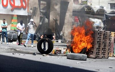 Palestinian protesters clash with Israeli security forces in the West Bank city of Hebron, May 14, 2021. (Wisam Hashlamoun/Flash90)