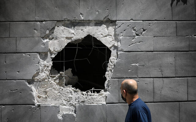 Israelis walk past damage caused to a building in the southern israeli city of Ashkelon, after it was hit by a rocket fired from Gaza into Israel, last night. May 14, 2021. Photo by Yonatan Sindel/FLASH90