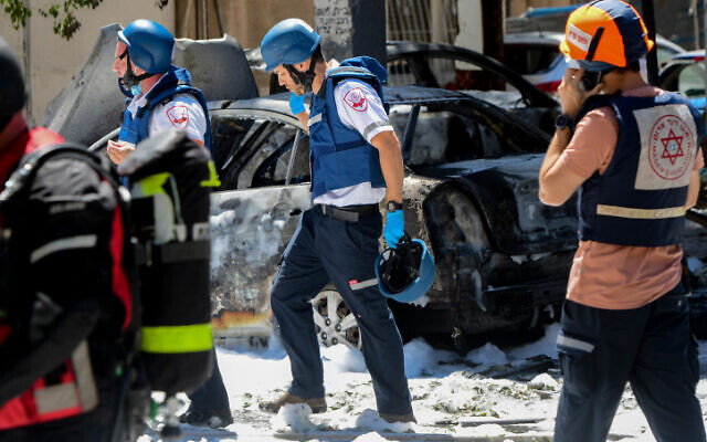 Police and rescue personnel at the scene of a rocket strike in Ramat Gan that left one person dead, on May 15, 2021 (Avshalom Sassoni/Flash90)