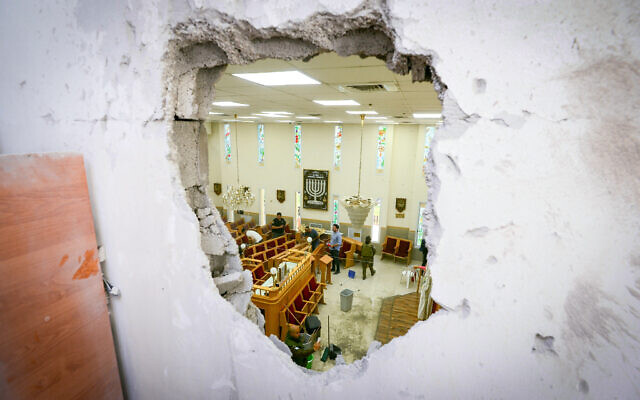 People clean up inside a damaged synagogue in Ashkelon, following a rocket attack from the Gaza Strip, on May 16, 2021. (Avi Roccah/Flash90)