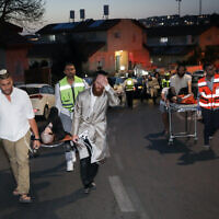 Medics and others evacuate injured after a bleacher collapsed in a syngogue in the Givat Zeev settlement on May 16, 2021. (Noam Revkin Fenton/FLASH90)