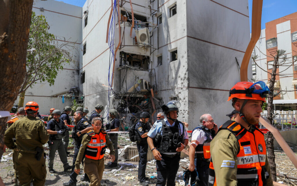 Rescue services are seen at a building in the southern port city of Ashdod that was hit by a rocket fired by Palestinian terrorists in the Gaza Strip, May 17, 2021 (Flash90)