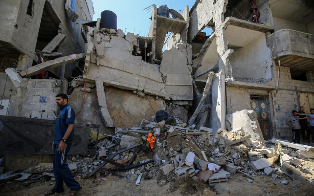 Palestinians inspect the damage following an Israeli air strike in Rafah in the southern Gaza Strip, on May 19, 2021 (Abed Rahim Khatib/Flash90)