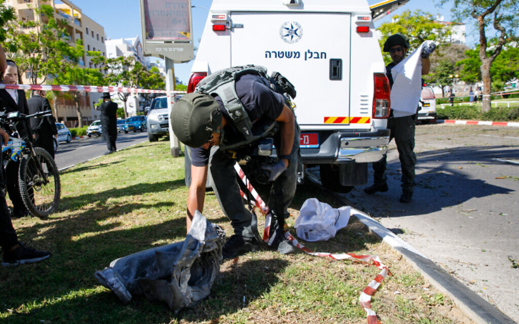 Security forces at the scene where a fragment of a rocket fired from the Gaza Strip landed in the southern Israeli city of Ashdod, on May 19, 2021 (Flash90)
