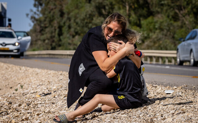 A woman and child take cover as a siren sounds a warning of incoming rockets fired from the Gaza Strip, on a road between Ashkelon and Sderot, southern Israel, on May 19, 2021. (Olivier Fitoussi/Flash90)