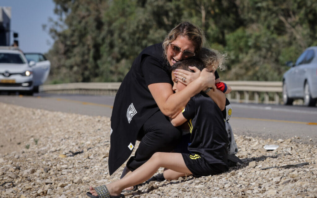 A woman and child take cover as a siren sounds a warning of incoming rockets fired from the Gaza strip in the city of Ashkelon, southern Israel, on May 19, 2021 (Olivier Fitoussi/Flash90)