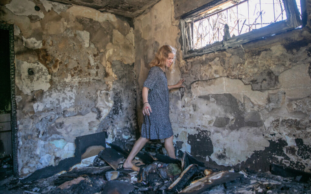 A woman walks through burnt rubble in Lod on May 19, 2021, as clean-up and rebuilding begin in the central city following riots a week earlier. (Yossi Aloni/Flash90)