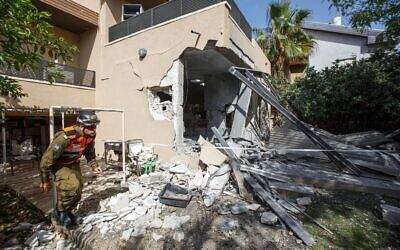 A soldier from the Israeli military's Home Front Command walks outside a house in the southern Israeli city of Ashkelon that had been struck by a Hamas rocket on May 20, 2021. (Edi Israel/FLASH90)