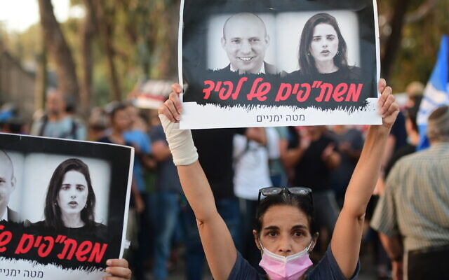 Right-wing protestors outside the home of Yamina MK Ayelet Shaked  in Tel Aviv on May 30, 2021. The sign with a picture of Shaked and Yamina leader Naftali Bennett reads 'Lapid's collaborators'  (Avshalom Sassoni/Flash90)